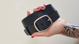 A woman holding a leather belt